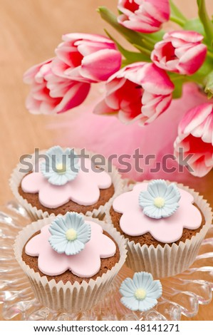 Mothers day cupcakes decorated with flower petals with spring tulips - stock photo