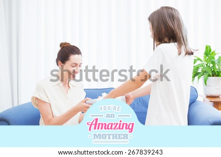 mothers day greeting against daughter giving her mother a present - stock photo