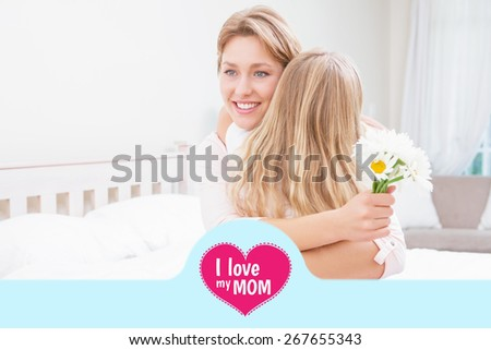 mothers day greeting against mother and daughter hugging with flowers - stock photo