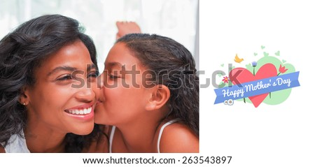 mothers day greeting against pretty woman lying on bed with her daughter kissing cheek - stock photo