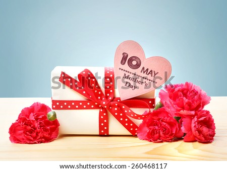 Mothers Day May 10th message with present and pink carnation flowers - stock photo