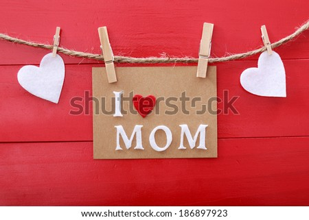 Mothers day message with felt hearts hanging with clothespins over red wooden board  - stock photo