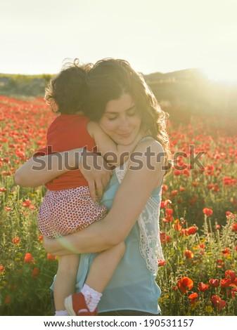 Mothers hug baby in sun light - stock photo