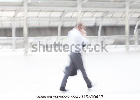 motion blur businessman talking on mobile phone - stock photo