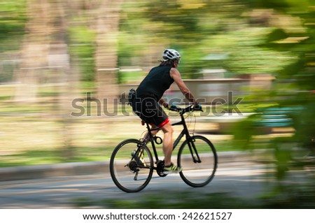Motion blur of a bike rider in public park - stock photo