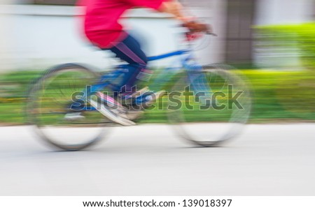 Motion blur of a bike rider on the street - stock photo