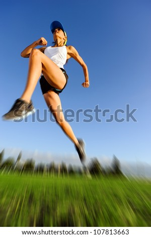 motion blur of athlete jumping outdoors with blue sky and green grass - stock photo