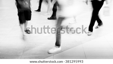 Motion blur people walking in fashion mall - black and white filter - stock photo