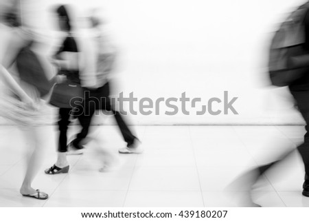 Motion blur people walking in rush hour or in hurry - black and white filter - stock photo