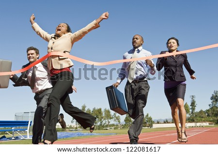 Motion blur shot of a cheerful business woman crossing the finish line with colleagues running in the background - stock photo