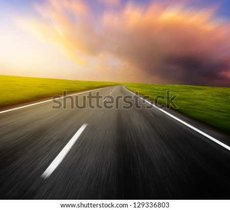 Motion blurred asphalt road through green meadow with sunset cloudy sky on the background - stock photo