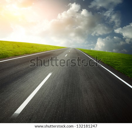 Motion blurred asphalt road through green meadows and cloudy sky - stock photo