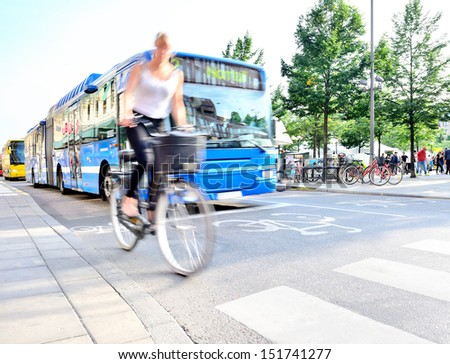 Motion blurred bicyclist in traffic - stock photo