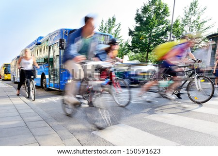 Motion blurred bicyclists in traffic - stock photo