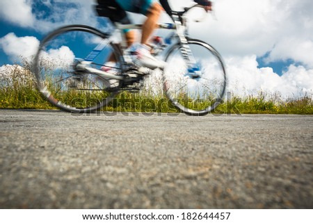 Motion blurred biker on a mountain road - stock photo
