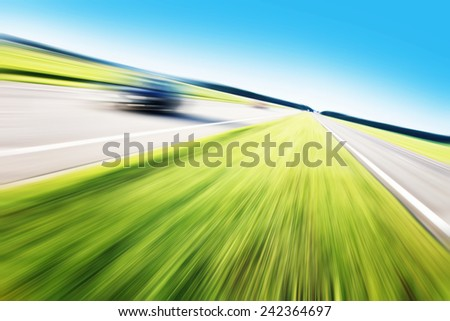 Motion blurred car on highway.Roadside view. - stock photo
