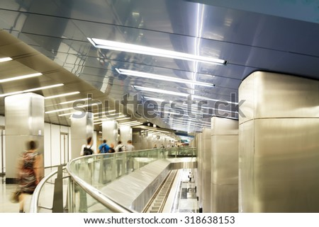 Motion blurred commuters walking on subway station. - stock photo