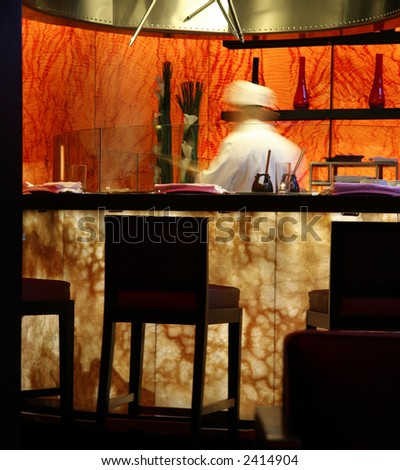 Motion blurred cook in a modern style Japanese restaurant - stock photo