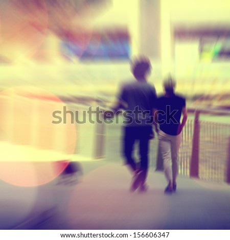 Motion blurred couple walking in the city - stock photo