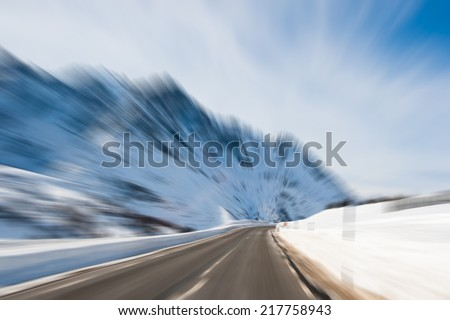 Motion blurred image of alpine road crossing mountain range - stock photo