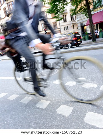 Motion blurred man in suit on bike - stock photo