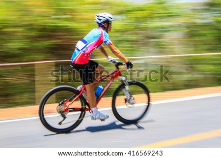 Motion blurred of the cyclist riding a bicycle in mountain bike  - stock photo