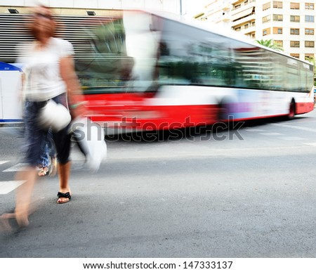 Motion blurred pedestrian and bus - stock photo