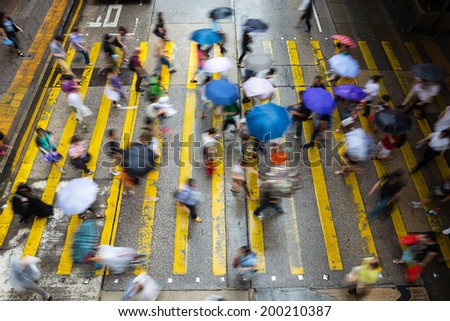 Motion blurred pedestrians crossing Hong Kong street in the rain - stock photo