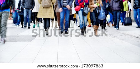Motion blurred pedestrians on walking / shopping street - stock photo