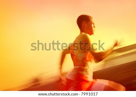 Motion Blurred runner, running past the stadium in a race - stock photo