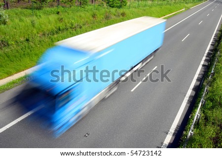 Motion blurred truck on highway. - stock photo