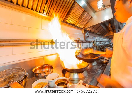 Motion chef fire hard cooking of restaurant kitchen,professional - stock photo