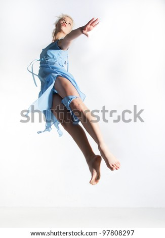 Motion. Dance. Sport. Young woman in blue dress jumping in studio - series of photos - stock photo