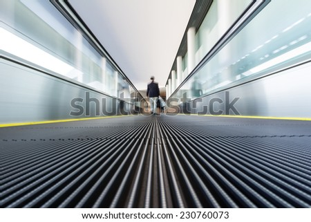 Motion of moving modern escalator way in the airport with a businessman - stock photo