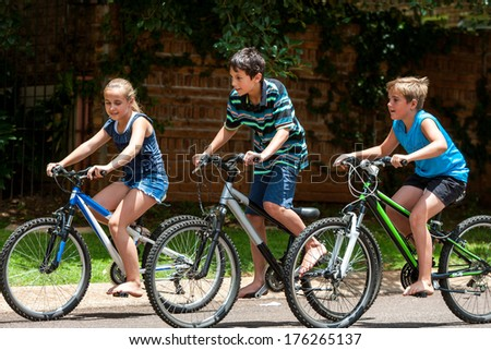 Motion shot of three kids competing with cycles outdoors. - stock photo