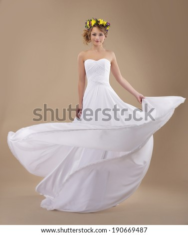 Motion. Woman with Wreath of Flowers and Fluttering Light Dress - stock photo