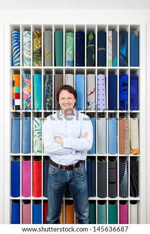 Motivated attractive young salesman standing with his arms folded in front of a colorful carpet display in an interior decorating shop - stock photo