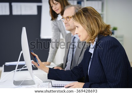 motivated business woman working with two colleagues - stock photo