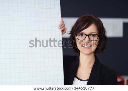 Motivated businesswoman giving a presentation standing alongside a flip chart with a blank sheet of paper and copyspace smiling happily at the camera - stock photo