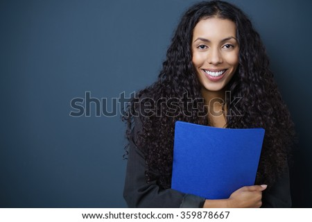 Motivated young African American job seeker clutching a blue CV in her hands standing against a blue background with copy space beaming at the camera - stock photo