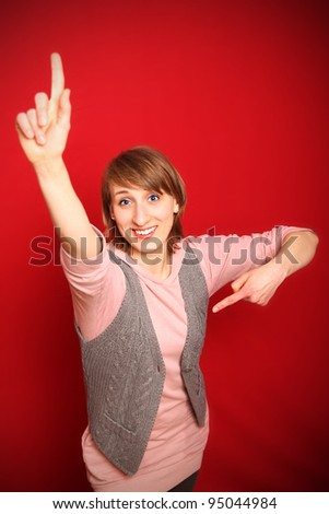motivated young woman in front of red background wanting to be picked aiming at herself and lifting finger - stock photo