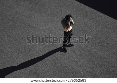 Motivation to run, exhausted runner resting tired after training outdoors, athletic jogger with muscular body taking break in city road, fitness and healthy lifestyle concept - stock photo