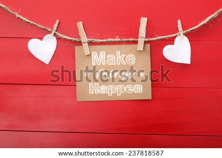 Motivational message card with hearts and clothespins on red wood - stock photo