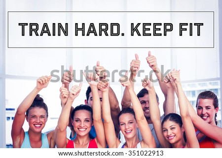 Motivational new years message against fit people gesturing thumbs up in exercise room - stock photo