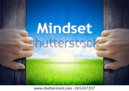 """Motivational quotes """"Mindset"""" . Hands opening a wooden door then found a texts floating among new world as green grass field, Blue sky and the Sunrise. - stock photo"""
