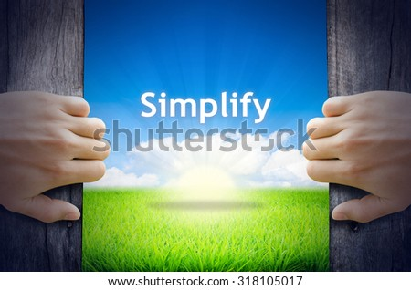 """Motivational quotes """"Simplify"""". Hands opening a wooden door then found a texts floating among new world as green grass field, Blue sky and the Sunrise. - stock photo"""