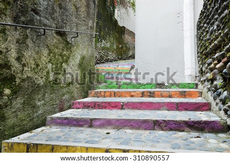 Motley stairs are paved with cobblestones along the wall overgrown with moth. The bent footway is stained of different colors. - stock photo