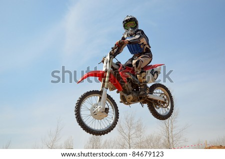 Motocross motorbike racer performs a jump efficient, hangs in the open air - stock photo