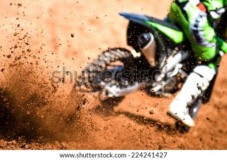 motocross racer accelerating in dirt track - stock photo