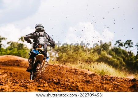 Motocross racer accelerating in dirt track - stock photo
